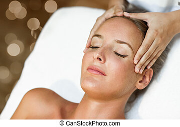 Young woman receiving a head massage in a spa center. -...