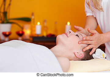 Young woman receiving a professional head massage