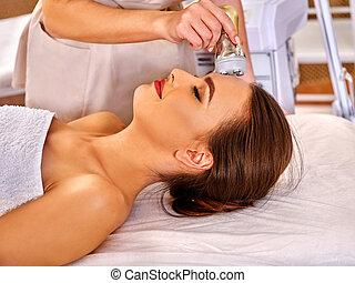 Young woman receiving electric facial massage. - young woman...