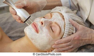 Young woman receiving electric facial massage.