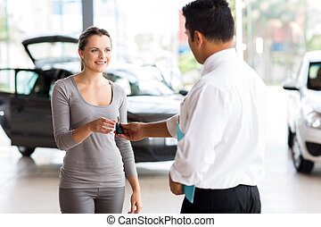 young woman receiving her new car key