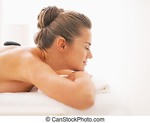 Young woman receiving hot stone massage