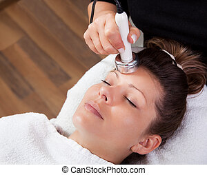 Young woman receiving laser therapy. Spa studio shot