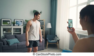 Young woman recording video of handsome male bodybuilder...