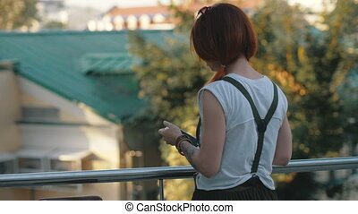 Young woman red hair holding and using mobile phone back...