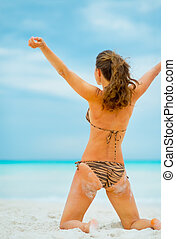 Young woman rejoicing on beach. rear view