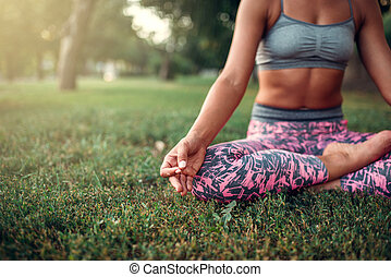 Young woman relax in yoga pose on the grass