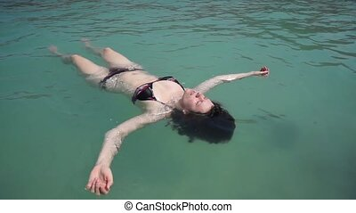 Young woman relax like a sea star in the ocean