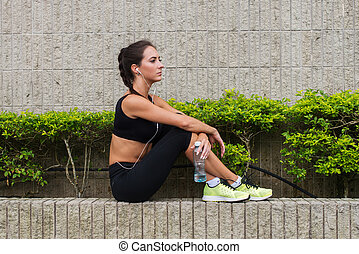 Young woman relaxing after doing sports, sitting against grey stone wall, listening to music, holding a bottle of water, preparing for running.