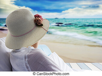 Young woman relaxing and looking sea on bed at the beach