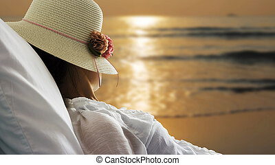 Young woman relaxing and looking sunrise in bed on the beach