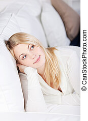Young Woman Relaxing And Smiling At Home on Sofa