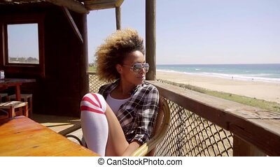 Young woman relaxing at a beachfront cafeteria sitting looking out over the ocean with a look of contentment