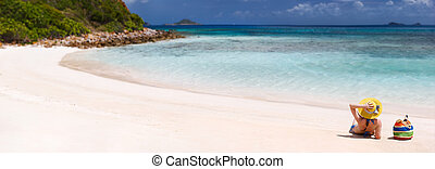 Back view of a young beautiful woman relaxing at white sand tropical beach, panorama with copy space perfect for banners