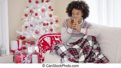 Young woman relaxing at home over Christmas sitting under a...