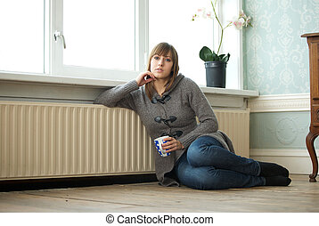Young woman relaxing at home with cup of coffee
