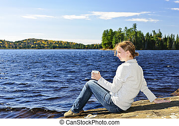 Young woman relaxing at lake shore
