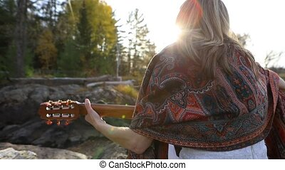 A blonde woman enjoying her time at a picnic in the forest. Artist enjoying with magnificent beauty of water. Musician inspired by sacred water