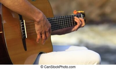 A musician girl getting inspiration at nature. A woman sitting on the stone near the fast-flowing river and playing guitar. Selective focus