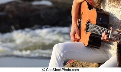Environment protectors at nature. Young musician woman playing guitar while sitting on the stone near the fast flowing mountain river