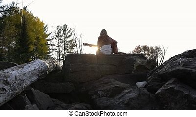 Long shot of a young woman sitting on the stone at nature. Woman musician playing acoustic guitar and enjoying fresh forest air