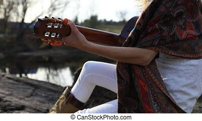 Traveler woman on vacation playing guitar in the forest near river. Girl playing guitar while sitting on the stone by the riverbank