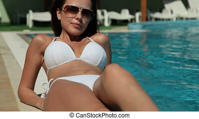 Young Woman Relaxing by the Pool, Looking at Camera