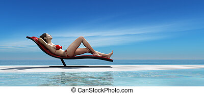 Young woman relaxing on a sunbed at the piece of beach. This...