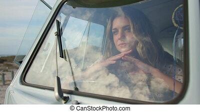 Young woman relaxing in camper van 4k - Front view of ...