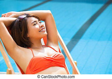 young woman relaxing in  chair beside swimming pool