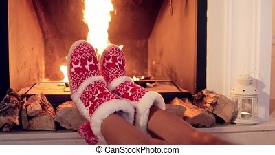 Young woman relaxing in Christmas booties - Young woman...