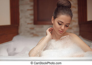 Young woman relaxing in foam jacuzzi bath spa, brunette enjoying the aromatherapy in wellness center. Beauty skin care treatment. Beautiful model relax in bathroom at home.