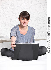 Young woman relaxing in front of a laptop computer