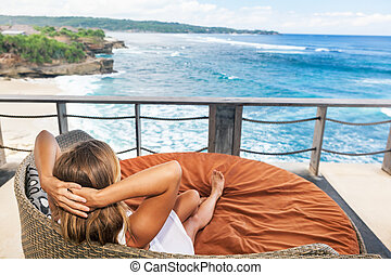 Young woman relaxing in lounge on veranda with sea view