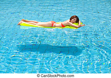 Young woman relaxing in swimming pool