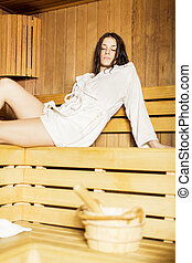 Young woman relaxing in the sauna