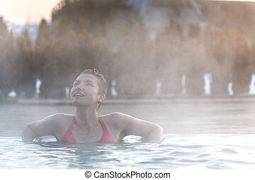 Young woman relaxing in thermal pool. - Happy young woman...