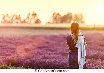 Young woman relaxing looking on lavender field at sunset