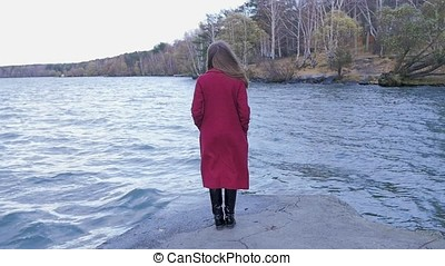 Young Woman Relaxing near Lake. Romantic beautiful woman enjoying her time and peaceful nature. Calm and cozy evening