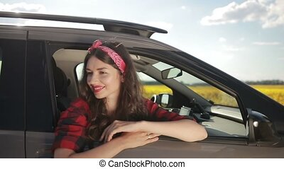Young woman relaxing on car door during road trip - Sensual...