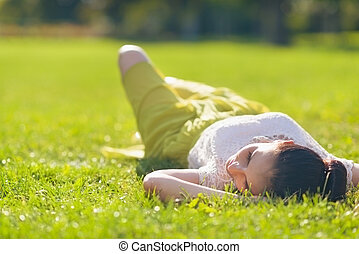 Young woman relaxing on grass. Rear view