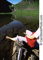 Young woman relaxing on rocks next to lake