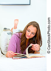 Young woman relaxing on sofa at home and reading book
