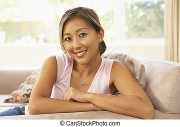 Young Woman Relaxing On Sofa At Home