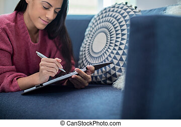 Young Woman Relaxing On Sofa At Home Writing In Journal