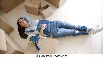Young woman relaxing on the floor after packing