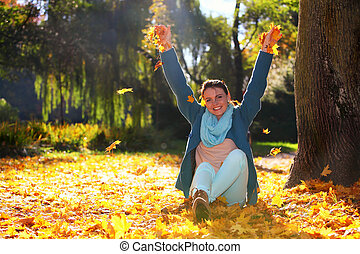 Young woman relaxing playing with leaves in autumn park - ...