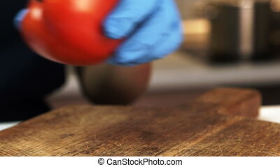 Young woman removes peduncle from red tomato on table in kitchen of apartment. Skilful female puts ripe glossy vegetable on flat wooden board and take away neatly dry part with hands in blue gloves. Housewife prepares round fresh fruit for cooking vegetarian salad.