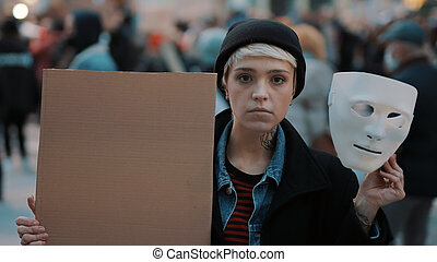 Young woman removing Theater mask while holding black cardboard in the crowd. Protest against discrimination
