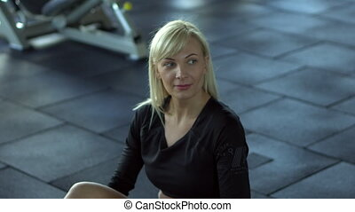 young woman resting between exercises in the gym - young...